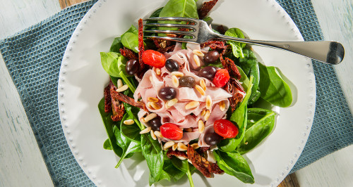 SALAD OF TENDER RAW SPINACH, HAM PIECES, TOASTED PINE NUTS, TAGGIASCA OLIVES AND SUN DRIED TOMATOES