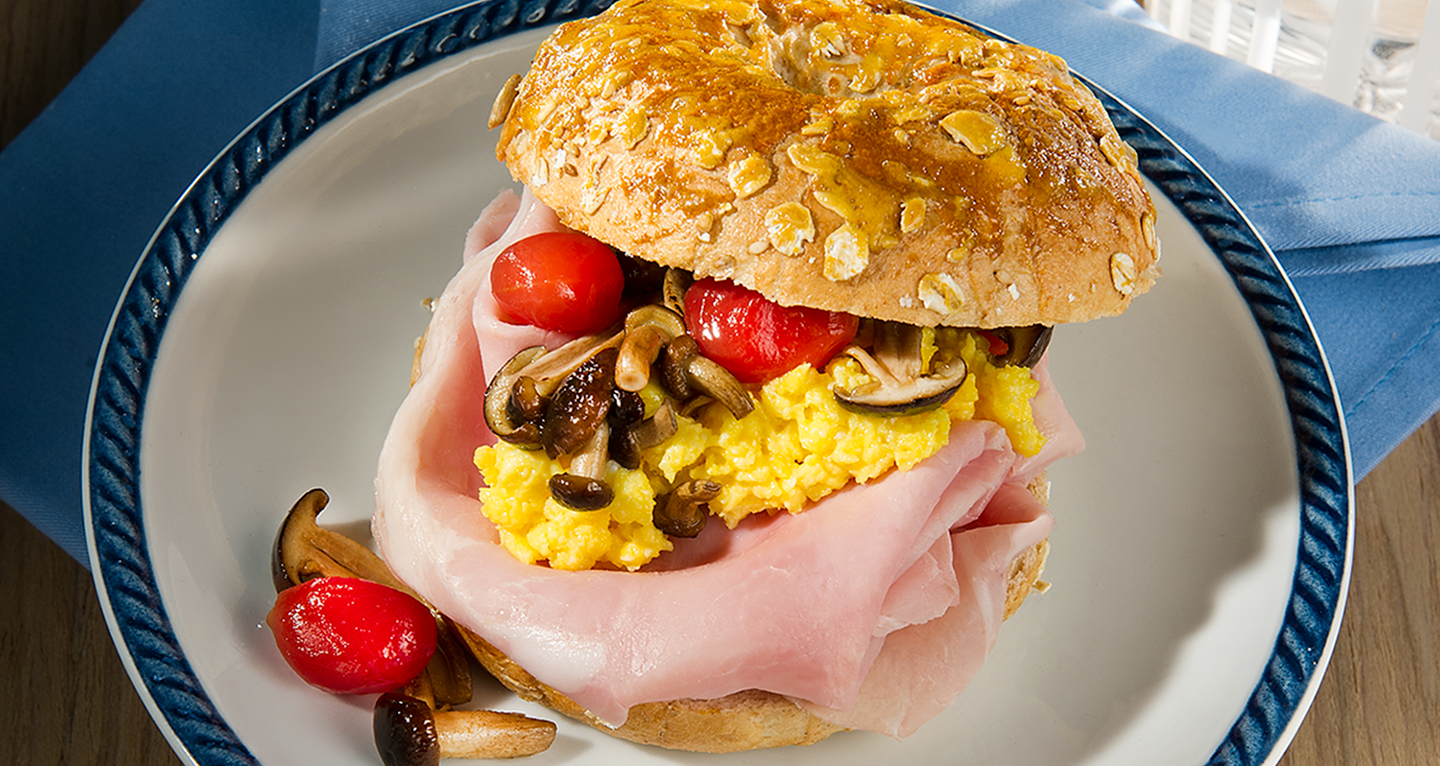 Bagels with cooked ham, scrambled eggs, tomato and browned mushrooms